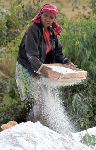 Woman sifting kaoline, product of weathering feldspar and mica, looking for gem fragments of tourmalines. J. Gajowniczek photo.